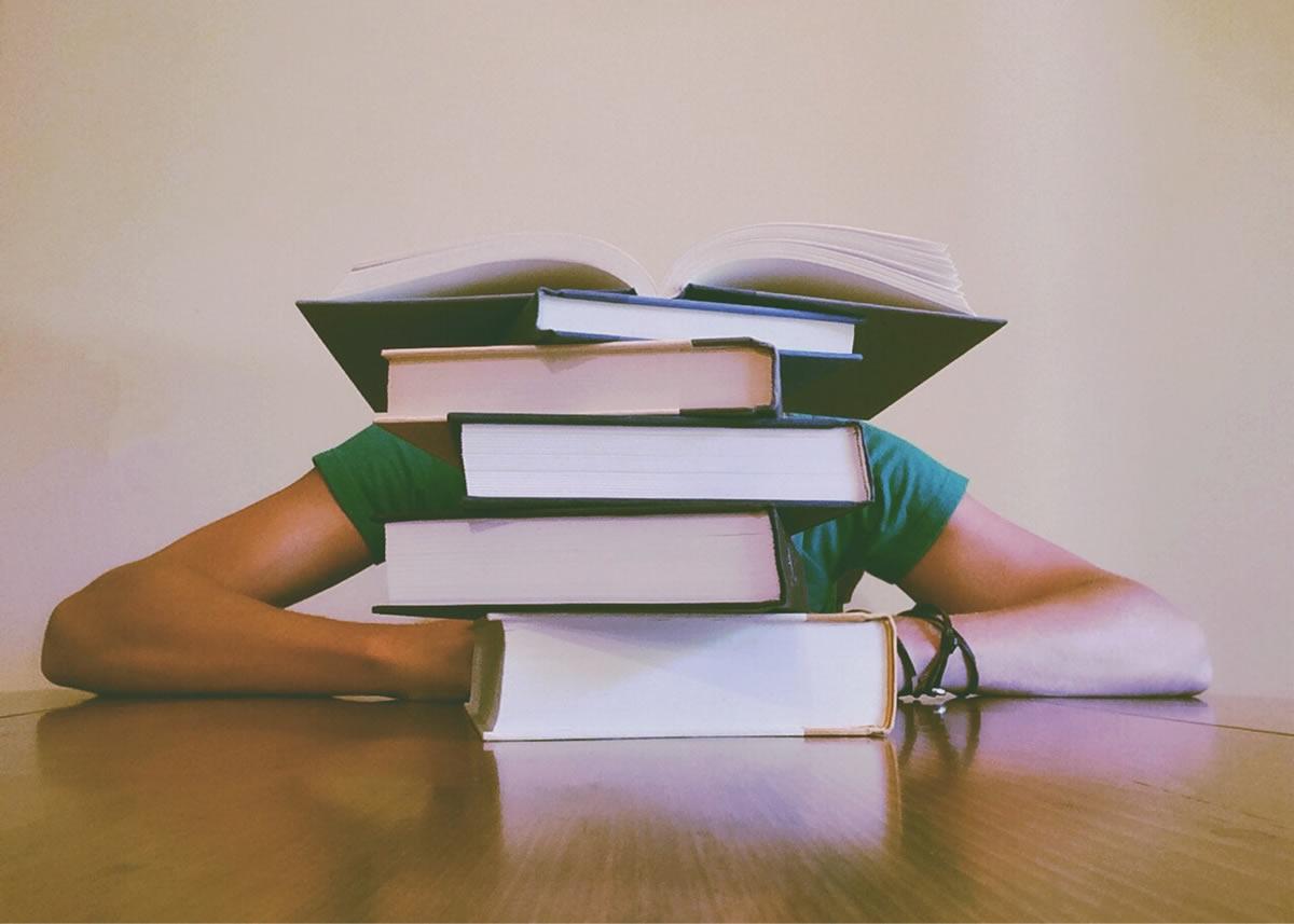 High school student behind books