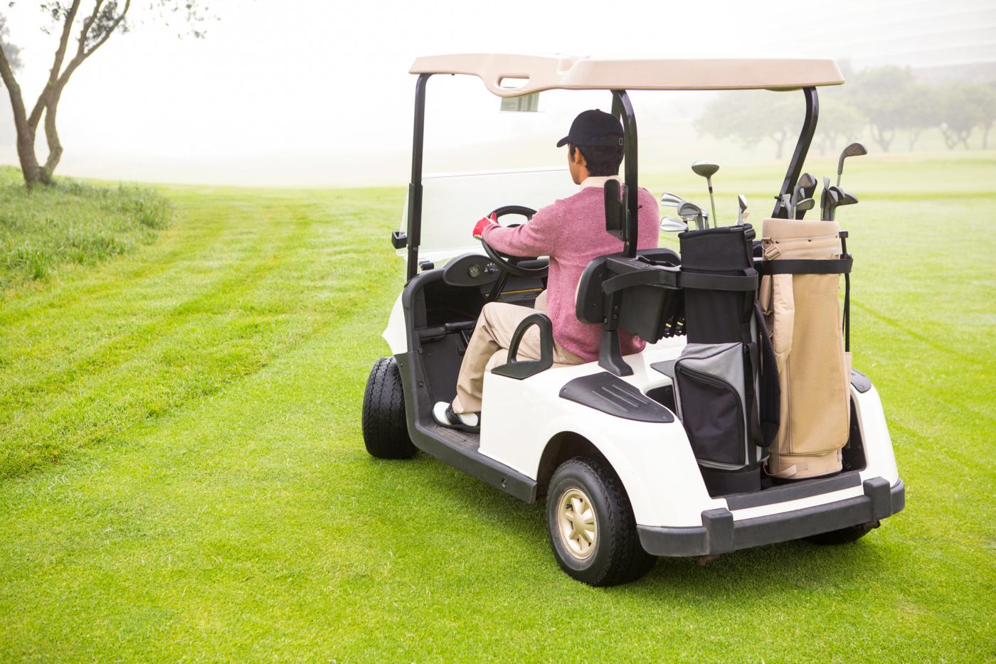Golfer driving golf cart