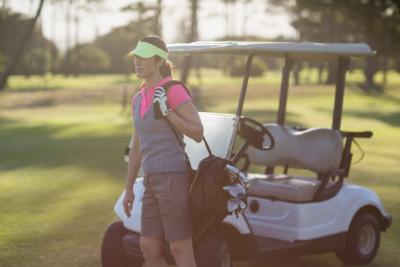 Golfingwomanstandingnexttocart