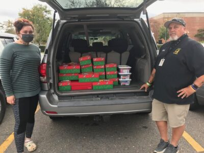 Keith Edgerton and Jaylynn Faughn stand next to a car loaded with shoeboxes to donate to Operation Christmas Child